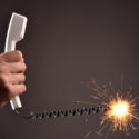 Male hand with a telephone and a burning cable like a fuse